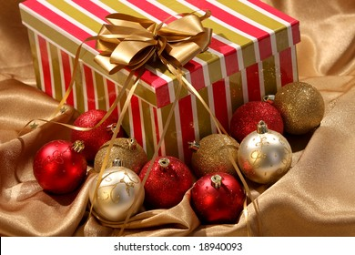 christmas gift box with a golden bow and ornament balls