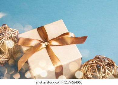 Christmas gift box with golden decorations on blue bacground. Gift box tied with golden ribbon. Holiday greeting card.
