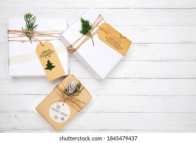 Christmas gift box with greeting tag - christmas present and pine leaves decoration on white wood table. Merry Christmas and New Year holiday background. top view.