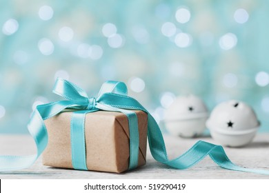 Christmas gift box and jingle bell against turquoise bokeh background. Holiday greeting card.