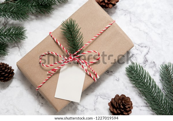 Christmas gift box with note card and tree branch decor on marble background. Flat lay, Top view with copy space