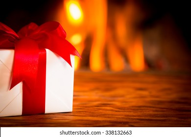 Christmas gift box on wood table against fireplace. Winter holiday concept