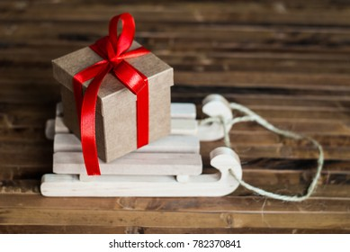 Christmas gift box on wooden sledges. Box with a red ribbon. Wooden background. Winter holidays. Top view.