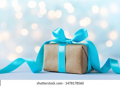 Christmas gift box or present box with beautiful blue ribbon against holiday lights background.