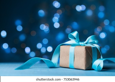 Christmas gift box or present with bow ribbon on magic blue bokeh background. Copy space for greeting card