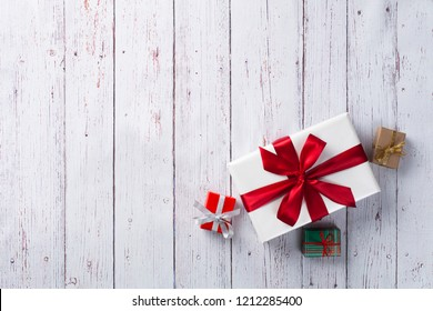 Christmas gift box. Christmas presents in boxes at white wooden table. Flat lay with copy space.