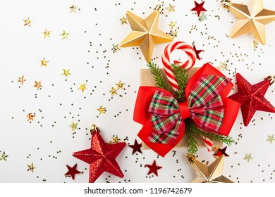 Christmas gift box with red ribbon and candy cone on white background. Top view.