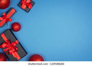 Christmas gift box with red ribbon on blue background. Holiday new year Top view with copy space for your design.