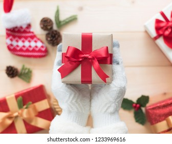 Christmas gift box with red satin ribbon decoration on giver hands in winter glove giving out on white pine wood table background for boxing day, snow seasonal holiday and new year celebration