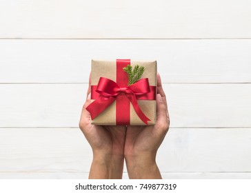 Christmas gift box with red satin ribbon and spruce twig decoration on giver hands giving out on white pine wood table background for boxing day, winter seasonal holiday and new year celebration