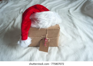 Christmas gift box and Santa hat on white bed