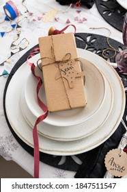 Christmas gift box tied with golden ribbon inside an elegant set of three dishes. The name Sean is on the tag.