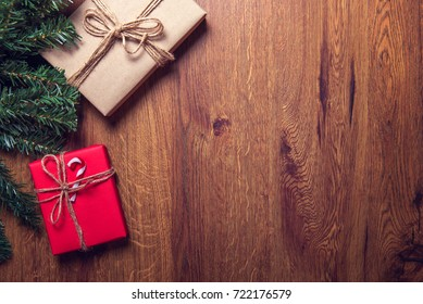Christmas gift box and tree branch decor on wooden table. Flat lay, Top view with copy space
