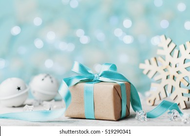 Christmas gift box and white jingle bell against blue bokeh background. Holiday greeting card