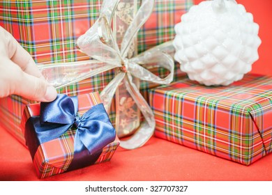 Christmas gift boxes with beautiful blue ribbon bow at red background. Concept of family gifts and presents at christmas eve and New Year