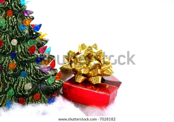 Christmas gift boxes with bow sit next to ceramic Christmas tree.