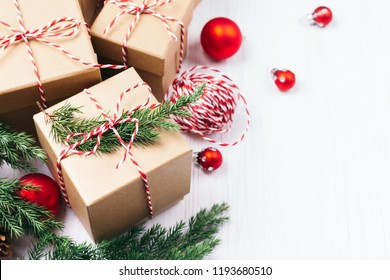 Christmas gift boxes collection with evergreen branches, candy cane Christmas rope and red Christmas balls. Angle view. Copy space.