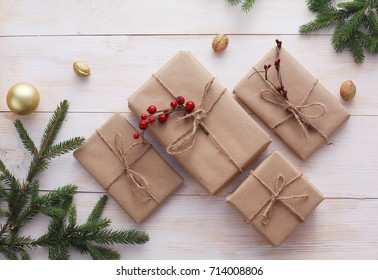Christmas gift boxes and fir tree branch on wooden table, flat lay