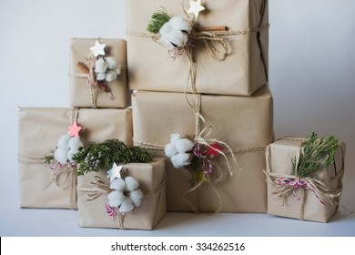 Christmas gift boxes with flowers and decorative objects Eco cotton, cinnamon, spruce branches and jute rope hank over white backg