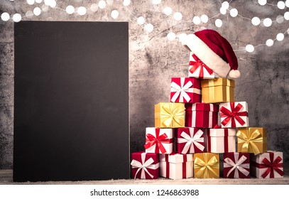 Christmas gift boxes in front of concrete wall shape of pyramid with Santa Claus hat on top. View with copy space for your text