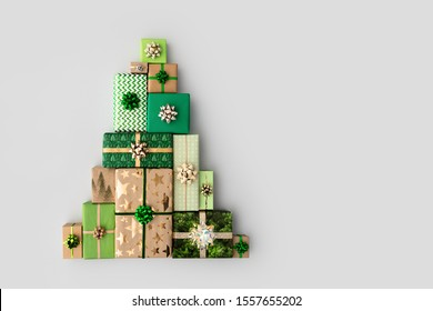 Christmas gift boxes laid out in the shape of a Christmas tree, overhead view