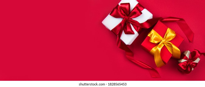 Christmas gift boxes with red and gold ribbons on a red banner background. Christmas and new year banner. Flat lay, top view, copy space, banner - Shutterstock ID 1828565453