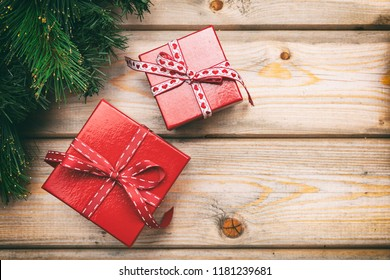 Christmas gift boxes with red ribbons on wooden background, copy space, top view