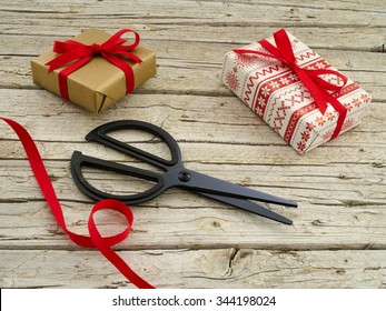christmas gift boxes, scissor and red ribbon on wooden background