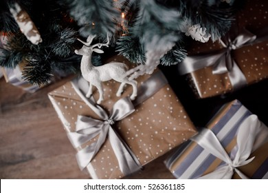 Christmas gift boxes under the fir tree. craft, silver, white and black colors of ribbons and paper. Deer toy on a box