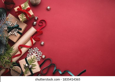 Christmas gift boxes, velvet ribbons, rolls of wrapping paper and decorations on red background.
