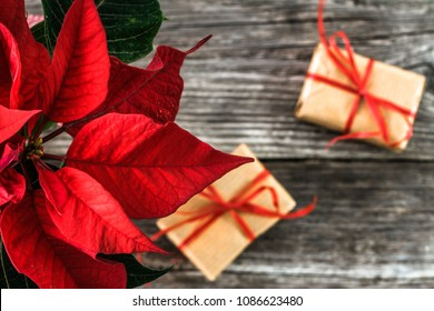 Christmas gift boxes, wrapped presents in rustic package and red poinsettia flower on wooden background