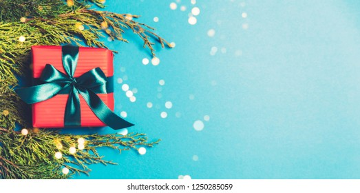 Christmas gift boxes wrapped in red paper on blue frozen background. Bright and festive Christmas concept. Top view, flat lay. Copy spce for text.