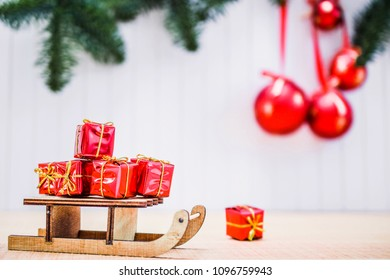 christmas gift boxes and xmas sleigh on wooden table over blurred background with christmas balls and