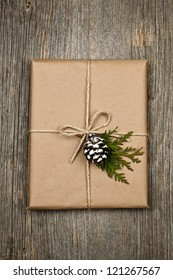 Christmas gift in brown wrapping and string with pine cone decoration on old wood background