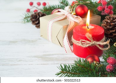 Christmas gift, candle and decorations on white wooden table.