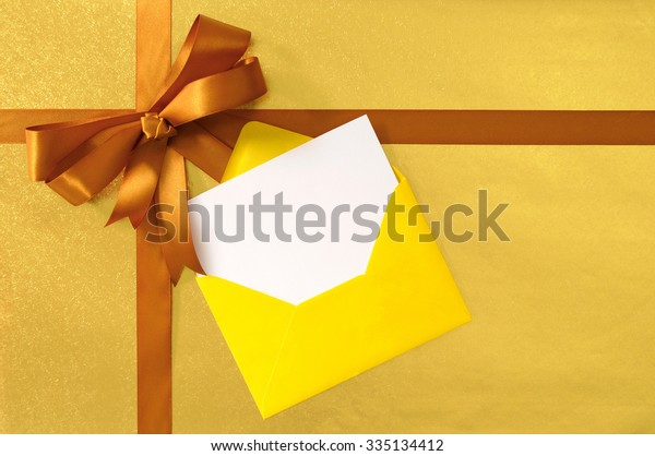 Christmas gift or card, gold ribbon bow on shiny paper background, yellow envelope, blank message