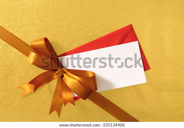 Christmas gift with card or label, gold ribbon bow on shiny paper background, red envelope, blank message