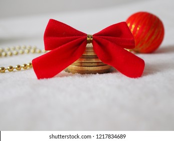 Christmas gift, coins on a white background with big red bow