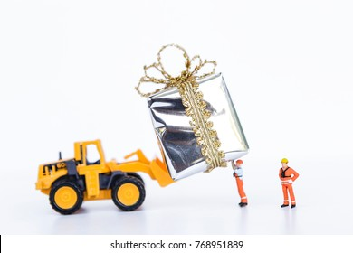 Christmas gift concept, front loader truck and miniature worker moving silver gift box on white background