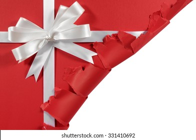 Christmas gift corner torn open, white ribbon bow, red paper background, copy space