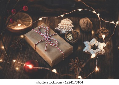 Christmas gift, decorated gingerbread cookies, orange and christmas lights on  wooden table. Decorated by festive decor. Dark rustic style. Top view. Toned with soft sepia old fashioned style.