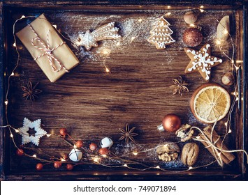 Christmas gift, decorated gingerbread cookies, fried orange slices, nuts, cinnamon, anis on wooden tray, decorated by festive decor. Dark rustic style. Christmas Postcard concept.