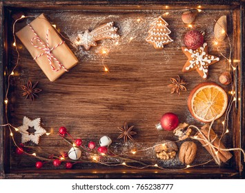 Christmas gift, decorated gingerbread cookies, fried orange slices, nuts, cinnamon, anis on wooden tray  over old wooden table, decorated by festive decor. Dark rustic style. Top view.