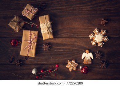 Christmas gift, decorated gingerbread cookies, anis and christmas lights on wooden table. Decorated by festive decor. Dark rustic style. Top view. Toned with soft sepia old fashioned style.