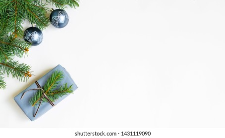 Christmas gift, fir branches on a white background. Flat lay, top view, copy space.