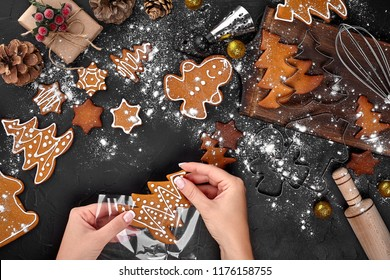 Christmas gift gingerbread on dark background. Biscuits in festive packaging. Woman is packaging Christmas gingerbread cookies with icing sugar. Top view