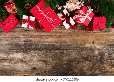 Christmas gift giving concept - christmas presents in red and white boxes on wooden table, flat lay with copy space