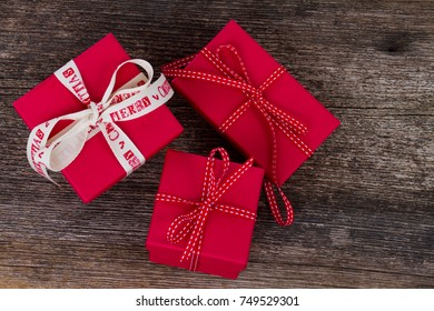 Christmas gift giving - pile of wrapped in red paper christmas gift boxes with ribbons on wooden background