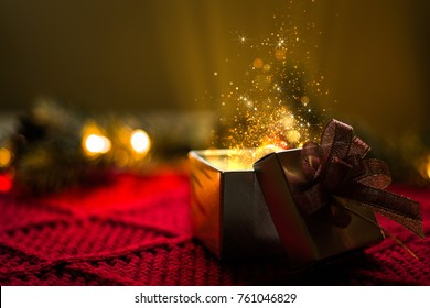 Christmas gift with gold particles magic lights.