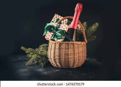 Christmas gift hamper with champagne and gift with green bow on black. Space for your greetings. Xmas.